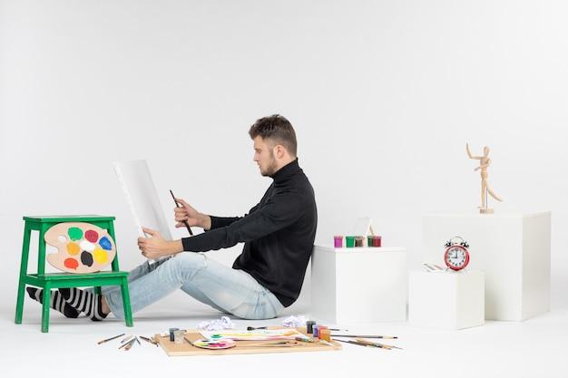Vue de face jeune homme essayant de dessiner la peinture avec pompon sur mur blanc artiste peinture art couleur peinture photo dessiner