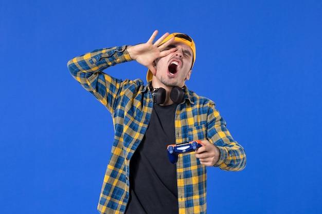 Vue de face d'un jeune homme excité avec une manette de jeu jouant à un jeu vidéo sur un mur bleu
