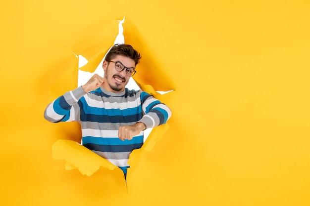 Vue de face jeune homme excité regardant à travers le mur jaune en papier déchiré