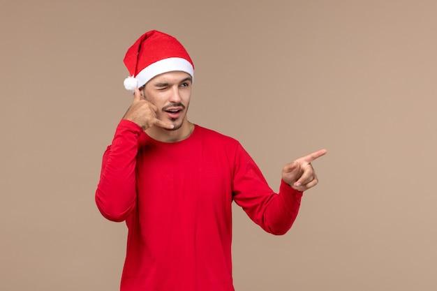 Vue de face jeune homme avec une expression clignotante sur fond brun émotion de vacances de noël