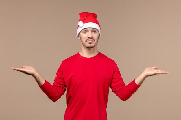Vue de face jeune homme avec une expression excitée sur le bureau brun vacances d'émotions de noël