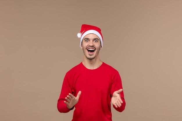 Vue de face jeune homme avec une expression excitée sur fond marron émotions vacances mâle