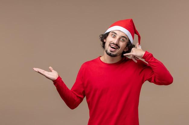 Vue de face jeune homme avec une expression excitée sur le fond marron vacances émotion noël