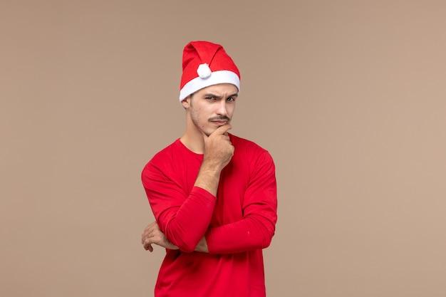 Vue de face jeune homme avec expression de la pensée sur fond marron couleurs de vacances d'émotion masculine
