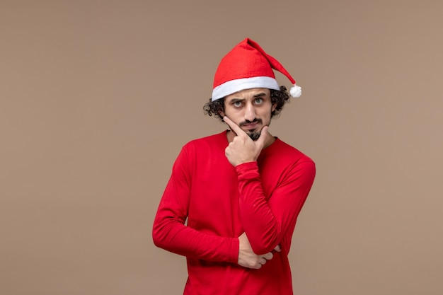 Vue de face jeune homme avec expression de pensée sur fond marron vacances d'émotion de noël