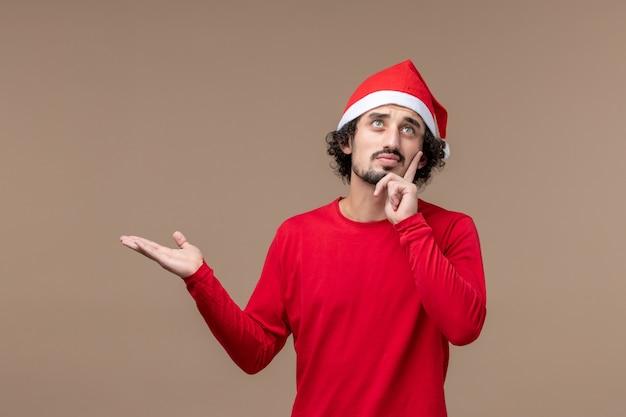 Vue de face jeune homme avec expression de pensée sur fond marron vacances émotion noël