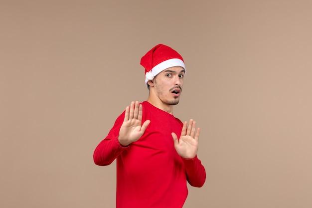 Vue de face jeune homme avec une expression prudente sur fond brun émotion vacances de noël