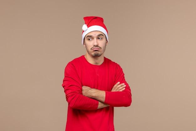 Vue de face jeune homme avec une expression triste sur fond marron émotions vacances couleur mâle