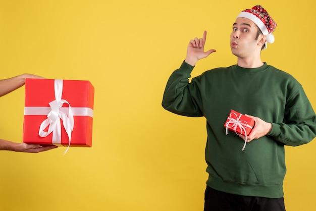 Vue de face jeune homme faisant doigt pistolet signe le cadeau dans la main féminine sur jaune