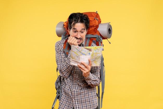 Vue de face jeune homme faisant de la randonnée avec sac à dos observant la carte sur fond jaune voyage d'entreprise campus couleurs de la forêt air