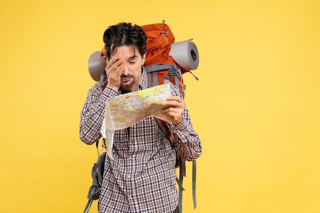 Vue de face jeune homme faisant de la randonnée avec sac à dos observant la carte sur fond jaune voyage d'entreprise nature campus forêt couleur air
