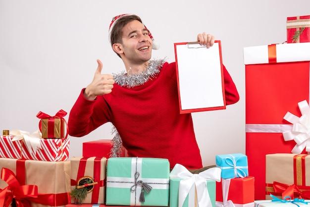 Vue de face jeune homme faisant signe de pouce vers le haut assis autour de cadeaux de noël