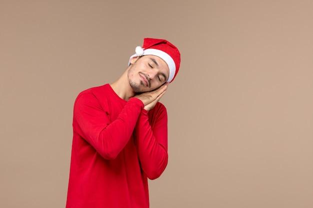 Vue de face jeune homme fatigué et essayant de dormir sur fond brun émotion vacances de noël