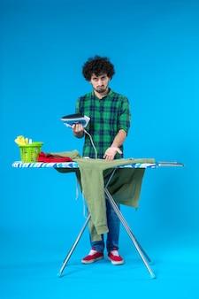 Vue de face jeune homme avec fer à repasser sur fond bleu machine propre humaine travaux ménagers couleur maison