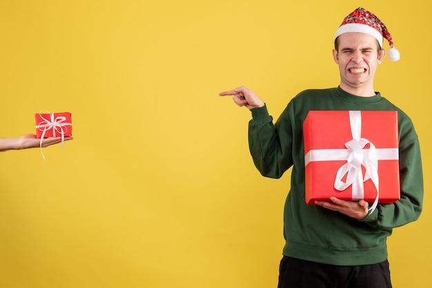 Vue de face jeune homme fermant les yeux pointant sur cadeau en main féminine sur jaune