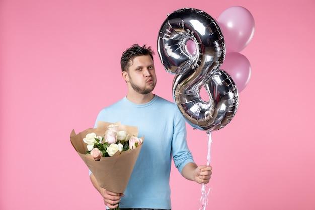 Vue de face jeune homme avec des fleurs et des ballons en mars présent sur fond rose date de l'égalité féminine journée de la femme mariage d'amour horizontal