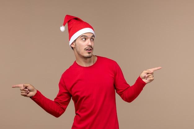 Vue de face jeune homme sur fond marron émotion vacances noël