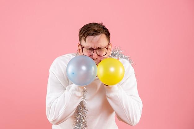 Vue de face jeune homme gonflant des ballons sur le fond rose