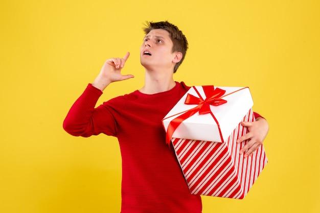 Vue de face jeune homme avec grand cadeau de noël sur fond jaune