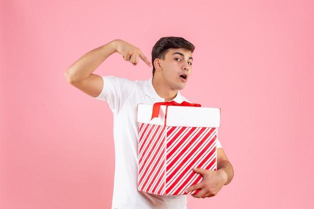 Vue de face jeune homme avec grand cadeau de noël sur fond rose