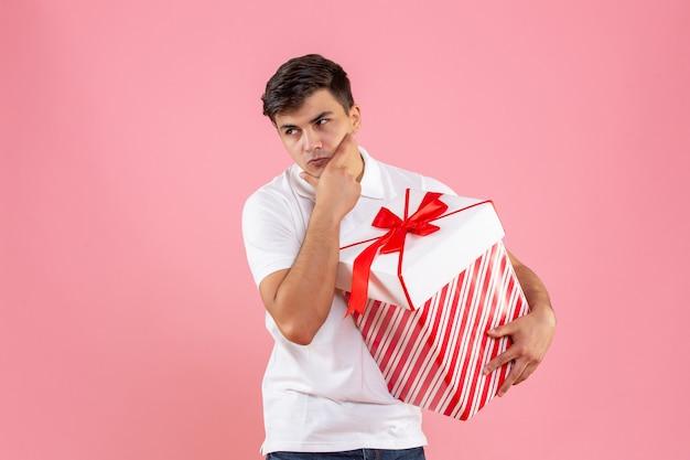 Vue de face jeune homme avec grand cadeau de noël pensant sur fond rose