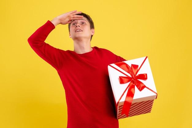 Vue de face jeune homme avec grand cadeau de noël à la recherche à distance sur fond jaune