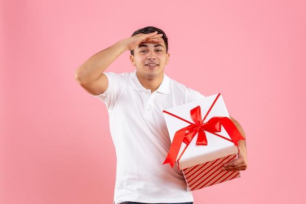 Vue de face jeune homme avec grand cadeau de noël à la recherche à distance sur fond rose