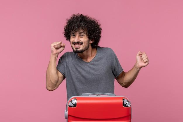 Vue de face jeune homme avec un grand sac rouge se préparant pour un voyage souriant sur un espace rose