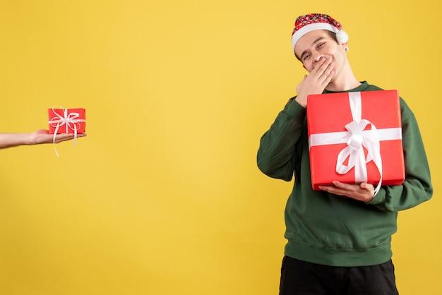 Vue de face jeune homme avec gros cadeau main humaine tenant cadeau debout sur jaune