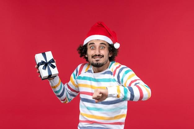 Vue de face jeune homme avec l'heure actuelle de vérification sur le mur rouge des émotions de vacances de nouvel an