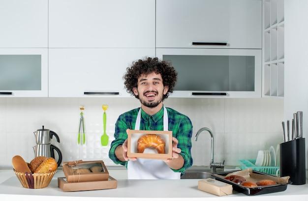 Vue de face d'un jeune homme heureux montrant une pâtisserie fraîchement préparée dans une petite boîte dans la cuisine blanche