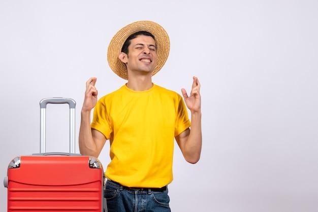 Vue de face jeune homme heureux avec t-shirt jaune montrant signe chanceux