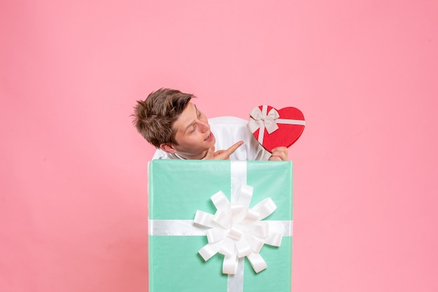 Vue de face jeune homme à l'intérieur présent avec cadeau sur fond rose