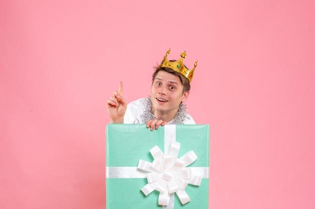 Vue de face jeune homme à l'intérieur présent avec couronne sur fond rose