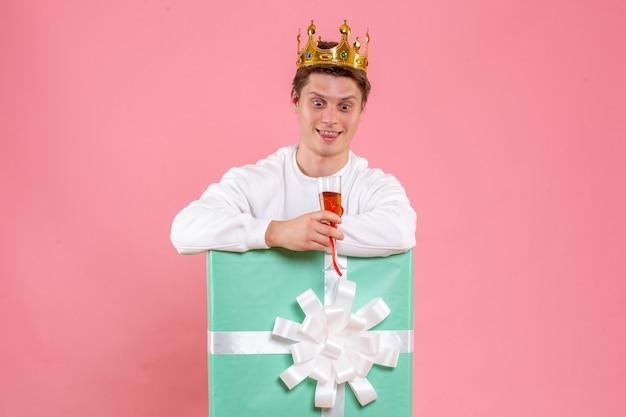 Vue de face jeune homme à l'intérieur présent avec couronne et verre de vin sur fond rose