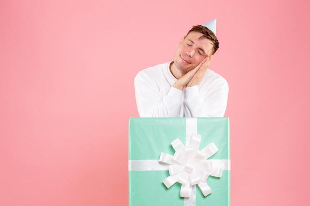 Vue de face jeune homme à l'intérieur présent faisant semblant de dormir sur fond rose