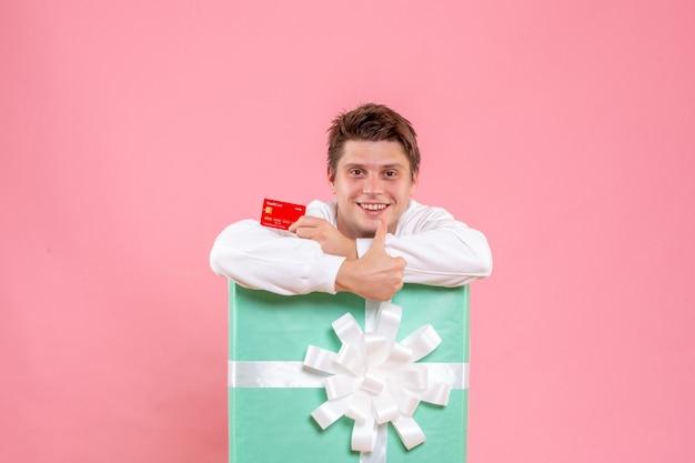 Vue de face jeune homme à l'intérieur présent tenant une carte bancaire rouge sur fond rose