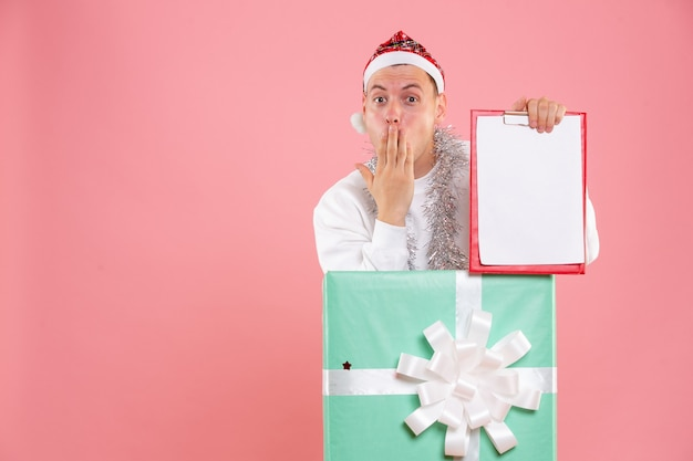 Vue de face jeune homme à l'intérieur présent tenant des notes de fichier sur le fond rose