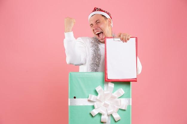 Vue de face jeune homme à l'intérieur présent tenant des notes de fichier se réjouissant sur fond rose