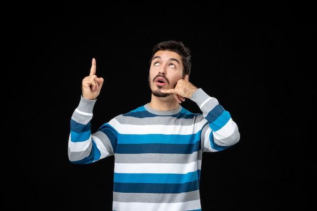 Vue de face jeune homme en jersey rayé bleu imitant un appel téléphonique