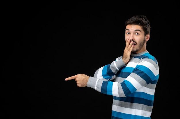 Vue de face jeune homme en jersey rayé bleu sur le mur noir