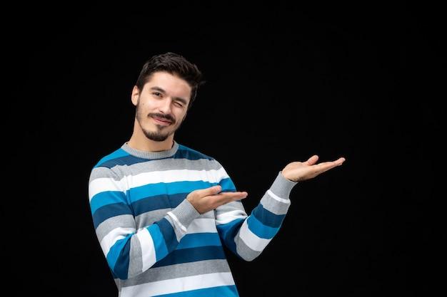 Vue de face jeune homme en jersey rayé bleu présentant ou montrant un produit