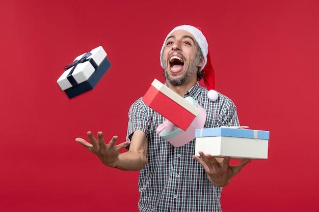 Vue de face jeune homme jetant joyeusement des cadeaux sur fond rouge