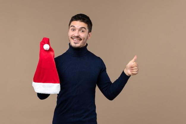 Vue de face jeune homme jouant avec bonnet rouge sur un fond marron émotions noël nouvel an