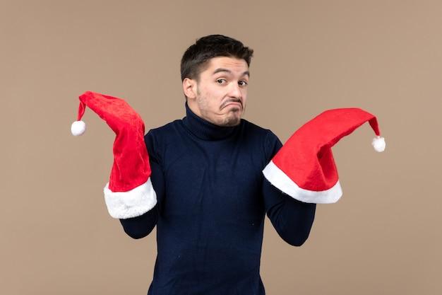 Vue de face jeune homme jouant avec des bonnets rouges sur fond marron noël émotions nouvel an
