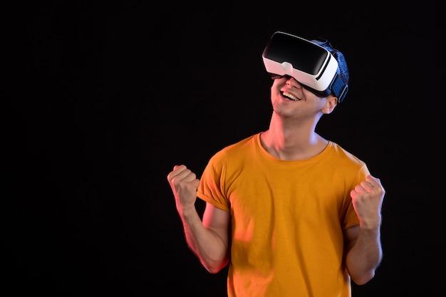 Vue de face d'un jeune homme jouant à la réalité virtuelle sur le mur sombre