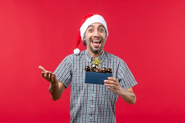 Vue de face jeune homme avec des jouets en plastique sur un bureau rouge