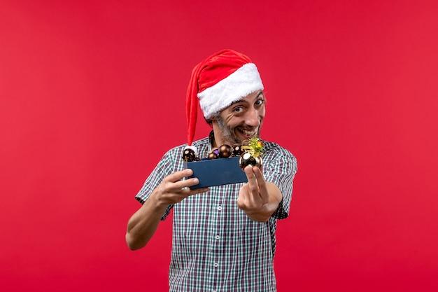 Vue de face jeune homme avec des jouets en plastique sur fond rouge