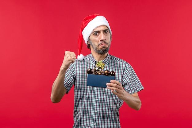 Vue de face jeune homme avec des jouets en plastique sur plancher rouge émotion nouvel an noël rouge