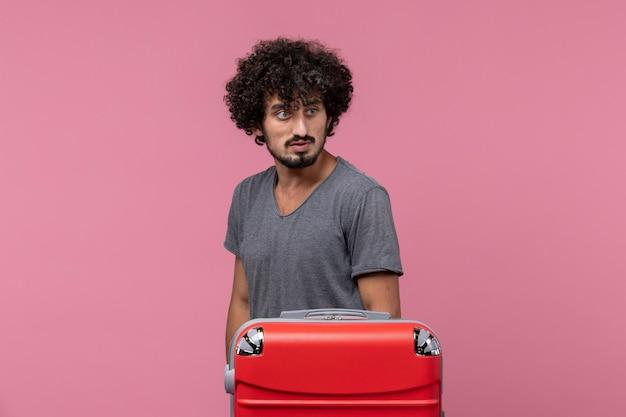 Vue de face jeune homme juste debout et se préparant pour un voyage sur un espace rose